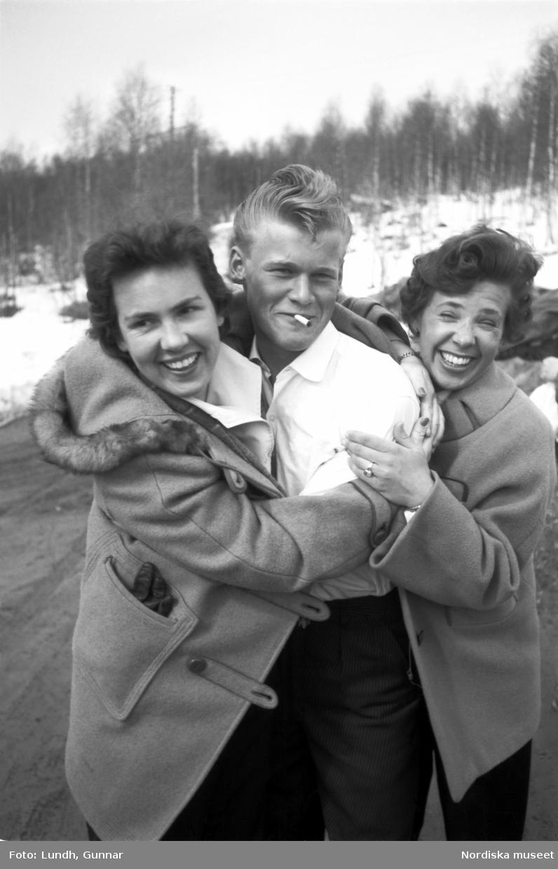 Tre tonåringar. Ung man med cigarett i munnen hålls om av två unga skrattande kvinnor.