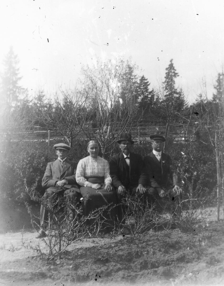 Tre män och en kvinna på en bänk.