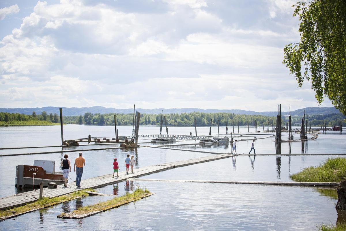 Foto av fløtingsanlegget. Flere personer går på flåter i vannet. (Foto/Photo)