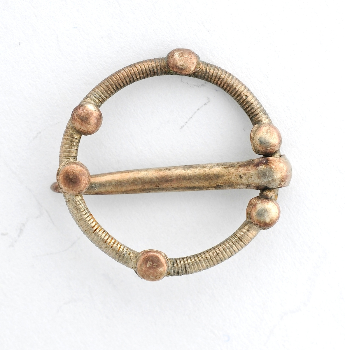 Sølje, sprette i sølv (manglar stempel). Smal, støypt ring med pålodda seks små, runde, plater. Laus tann.