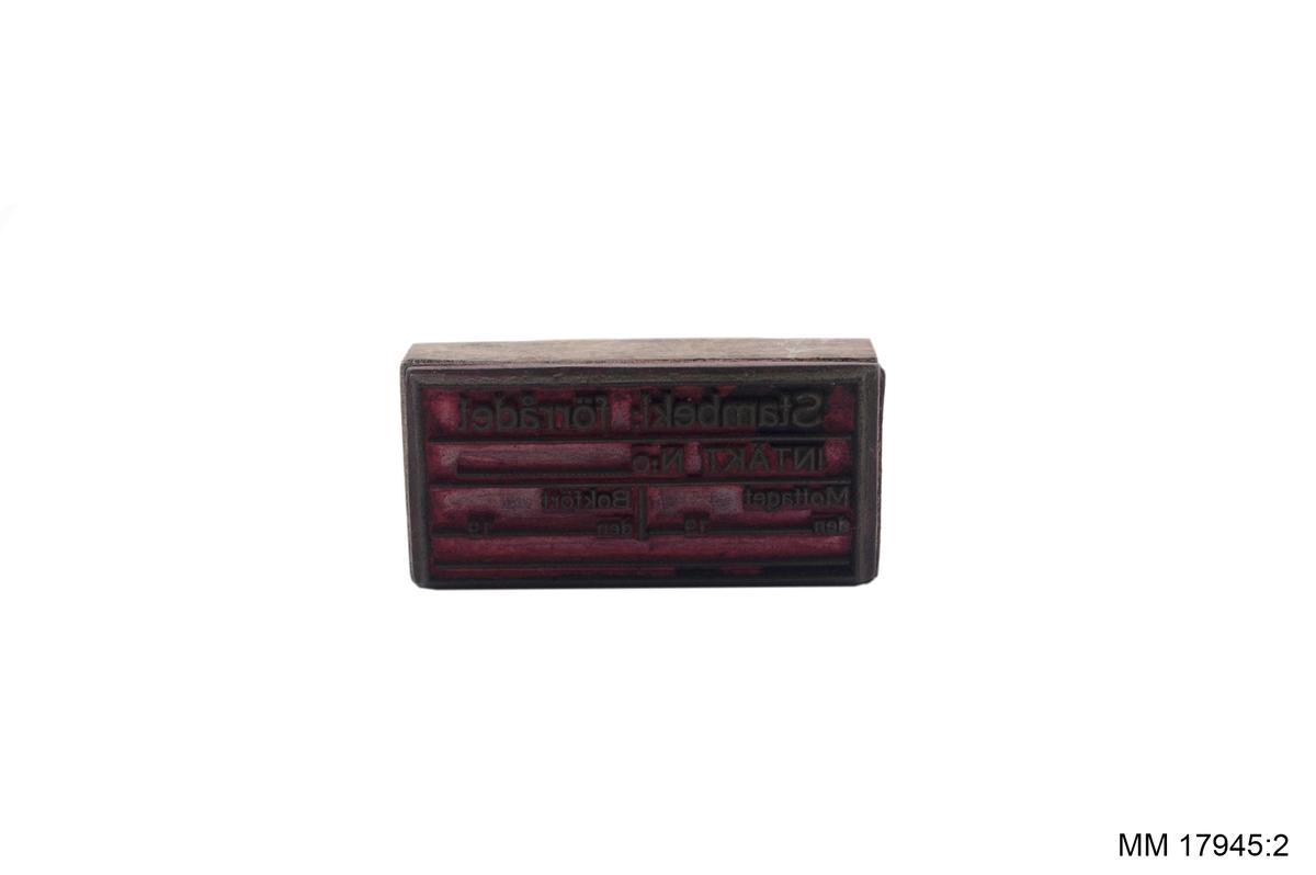 Stämpel med träskaft och gummerad dyna försedd med text rörande beklädnadsförrådet. Spår av svart färg.
