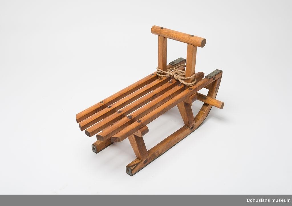 """Helt i trä, metallskruvar, medarna järnskodda. Uppstående handtag framtill. Snöre att dra kälken med fastsatt framtill. Handtaget av furu, resten tillverkat i en kombination av furu- och lövträ. Tunt lacklager som ytbehandling. Spräckta trädelar. På undersidan skrivet med blyerts: """"J.A. Grundberg"""". Släkt- och personuppgifter se UM026024"""