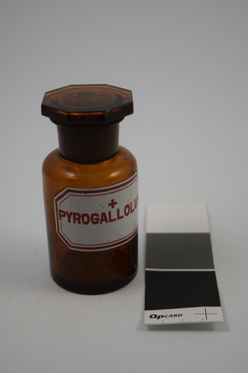 """Glassflaske, brun med brun propp. Påført etikett; hvit med rød skrift. Ett rødt kors - betyr at innholdet er giftig. Pyrogallolum, """"tretjære"""", ble brukt i salver mot eksem."""