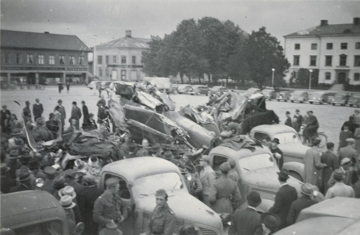 Soldater och civila samlade kring lastbil med flygplansvrak på flaket.