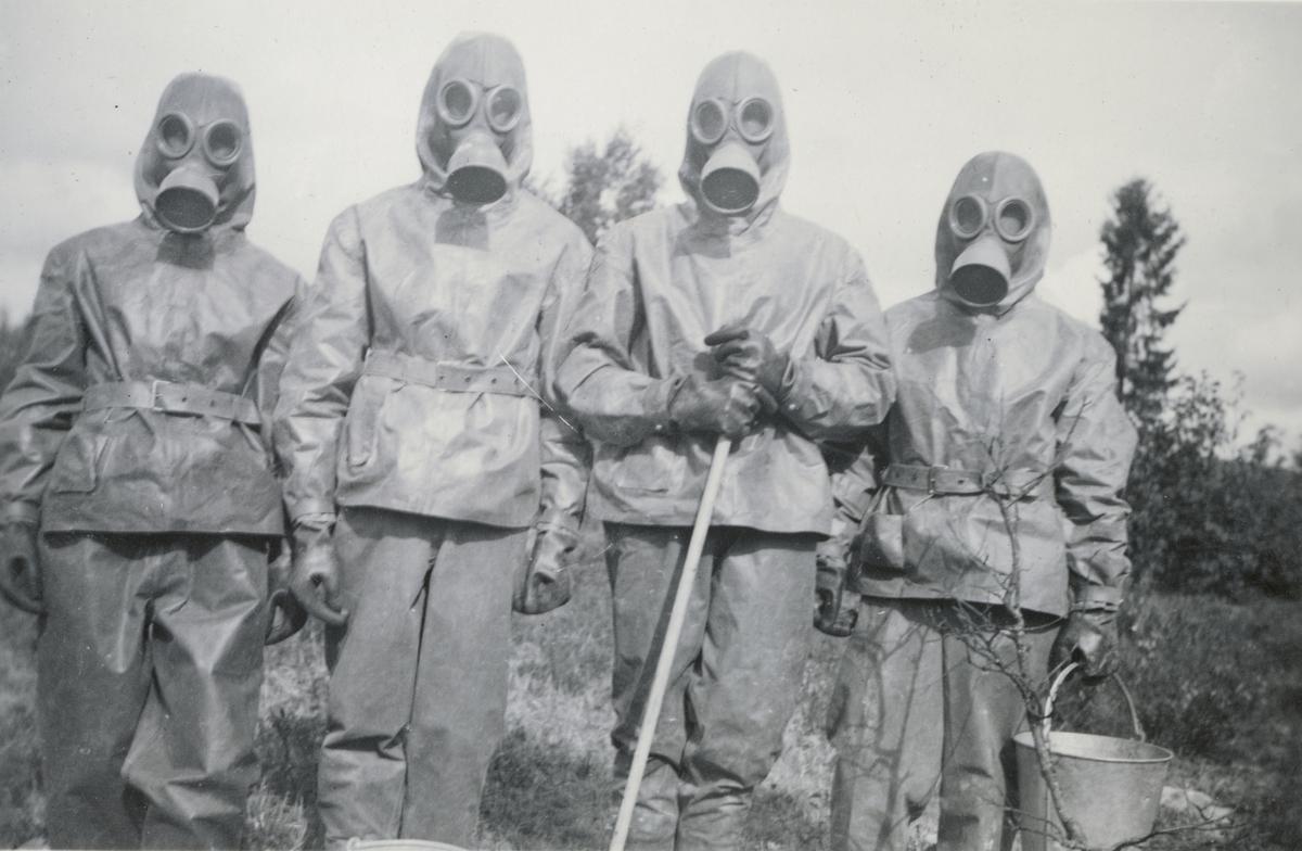 Gruppbild med soldater från Södermanlands regemente I 10 klädda i gasmask och skyddskläder.