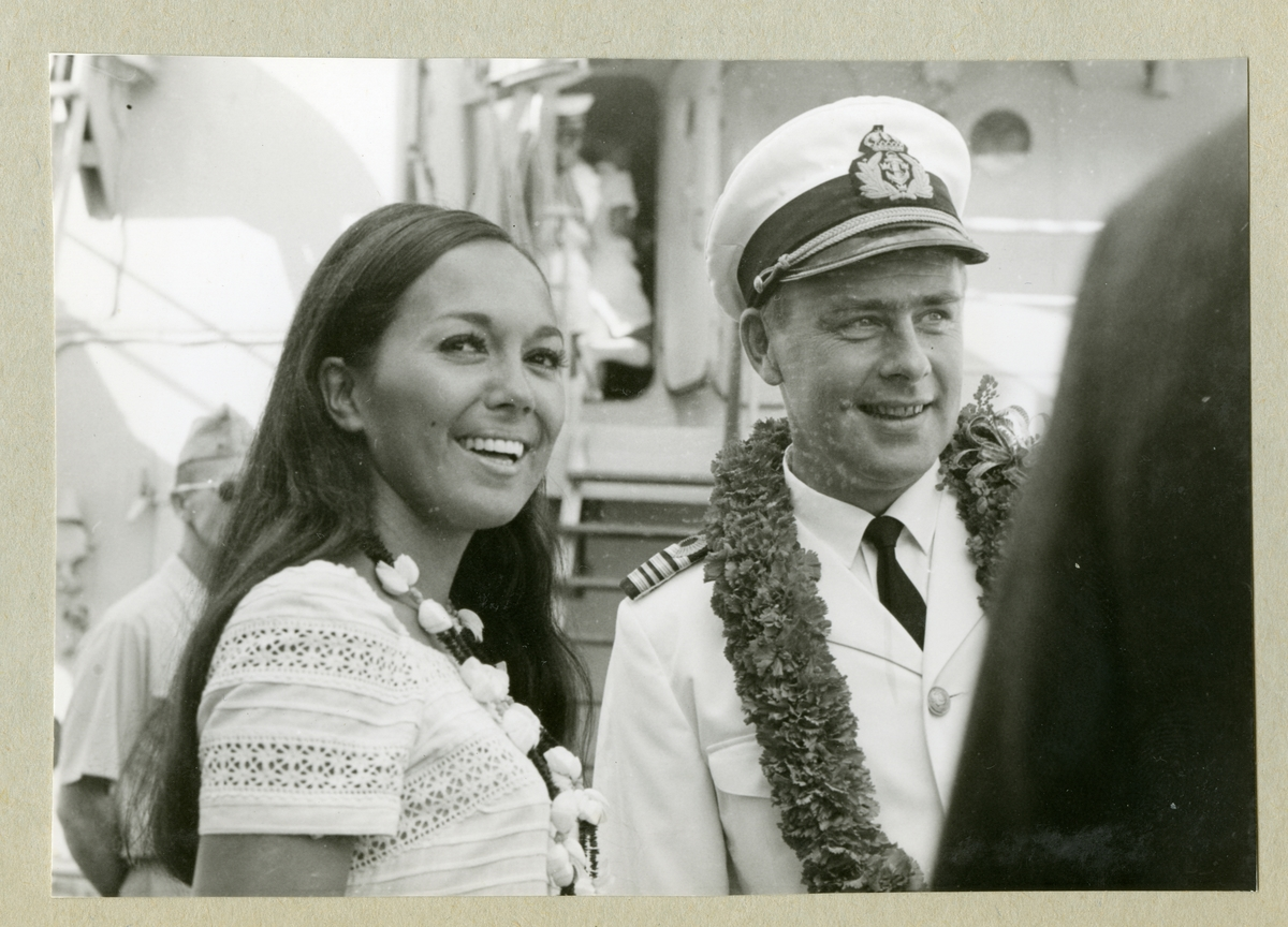 Bilden föreställer en kvinna och en besättningsman i vit uniform. Runt halsen är de utsmyckade med halsband. Bilden är tagen under minfartyget Älvsnabbens långresa 1966-1967.