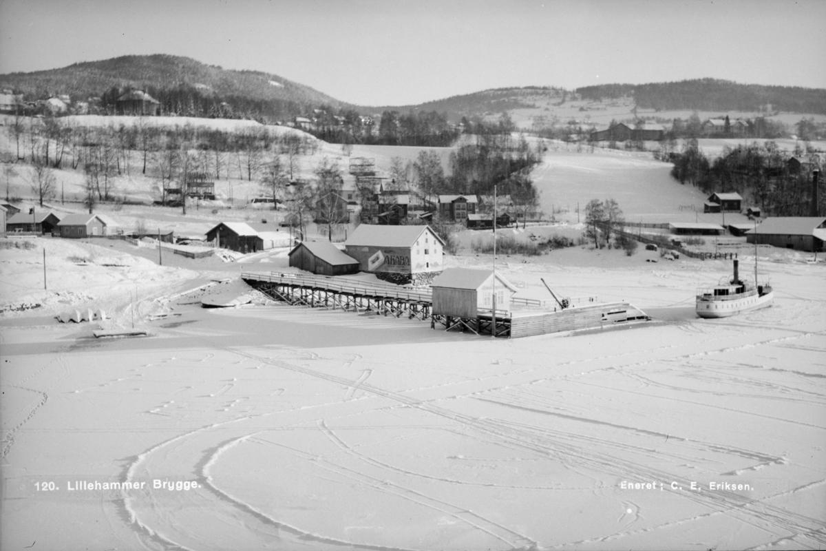 Vinter ved Lillehammer brygge. Oppe til venstre villaen til høyesterettsadvokat Axel Thallaug, bygd i 1918. Fra 1938 Nansenskolen. Oppe til høyre Suttestad gård.  MS Lillehammer ligger i vinteropplag.