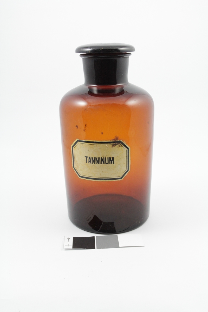 Standglass med vid hals, brun. Brukt til pulver.  Hvit merkelapp, sort skrift. Tannin ble brukt som stoppende middel.