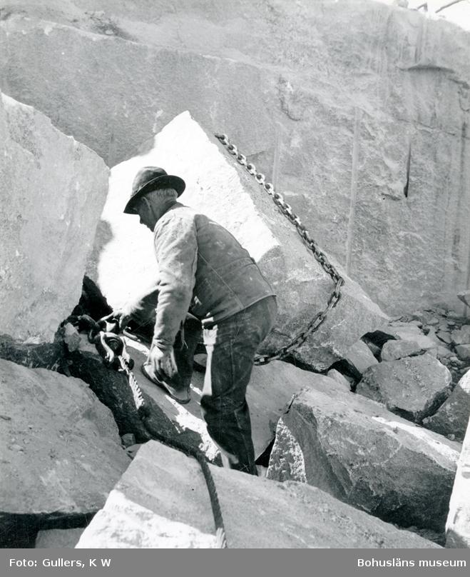 Stenhuggare förbereder för flyttning av ett stenblock, runt blocket är en kätting dragen