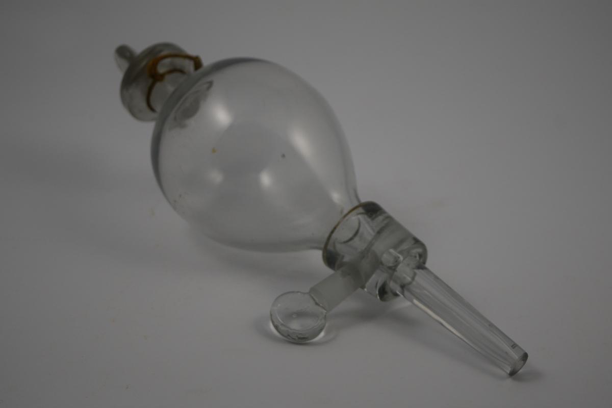 Skilletrakt av glass. Inntaket med propp i toppen og nede. Brukt i laboratoriet til å skille organisk væske fra uorganisk væske.