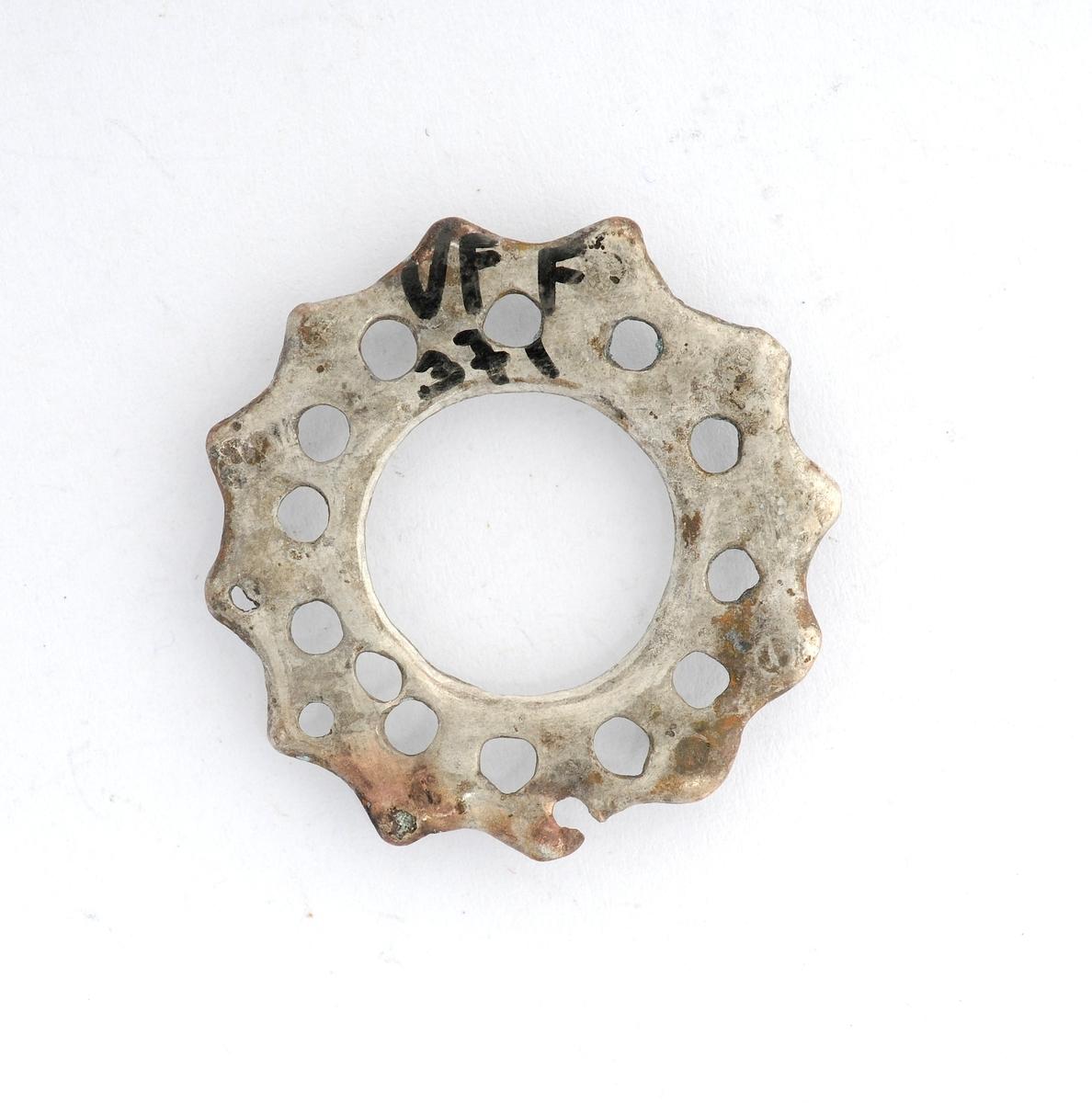 Sølje, støypt i messing, forsølva (?). Rund 12- tagga rosett med open sirkel i midten. Ring for vedheng på kvar tagg, fire manglar. Manglar tann (nål).