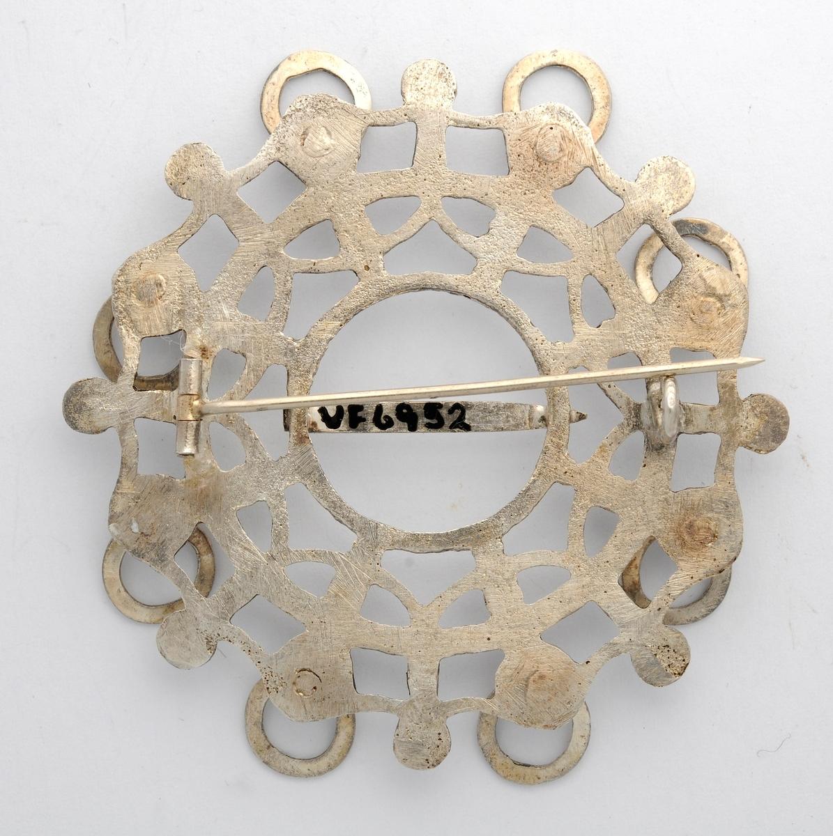 Sølje i sølv (utan stempel), støypt og med mønster på framsida. Rundt kanten åtte hemper med ringar i. Tanna er etterlikna etter gamle søljer, men fastlodda. Moderne nål på baksida.