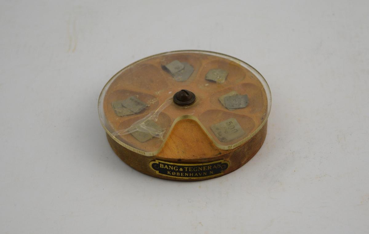 Rund loddsats, trebunn med groper og plastlokk. I gropene ligger små lodd; 3 stk. 500 mg., 6 stk. 200 mg., 1 stk. 100 mg.