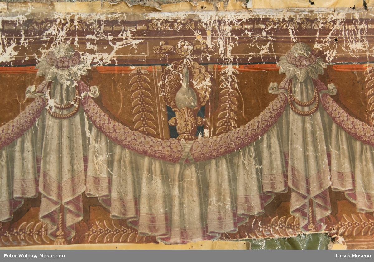 Tapeten er påmalt tapetborder og brystning. Fra Hovland gård i Larvik. Den øverste, brede borden: Gerlander/draperi med fuglemotiv (duer?) innfelt. Den nederste, smalere borden: Tekstilbord med blomster.