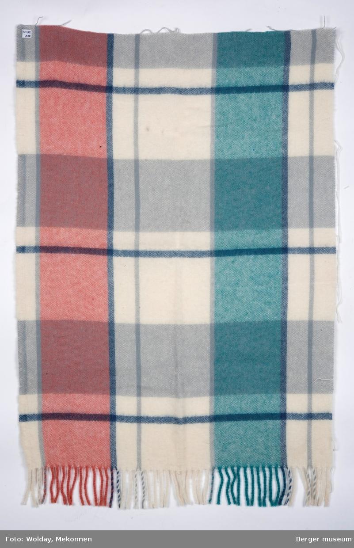 En avlang pleddprøve i rutemønster, med frynser i ene kortrtenden. Prøven har avklippede sidekanter. Mønsteret består av smale og brede striper, der de smale er mørk eller lys grå, de brede feltene er rosa, grønne og hvite og grå.