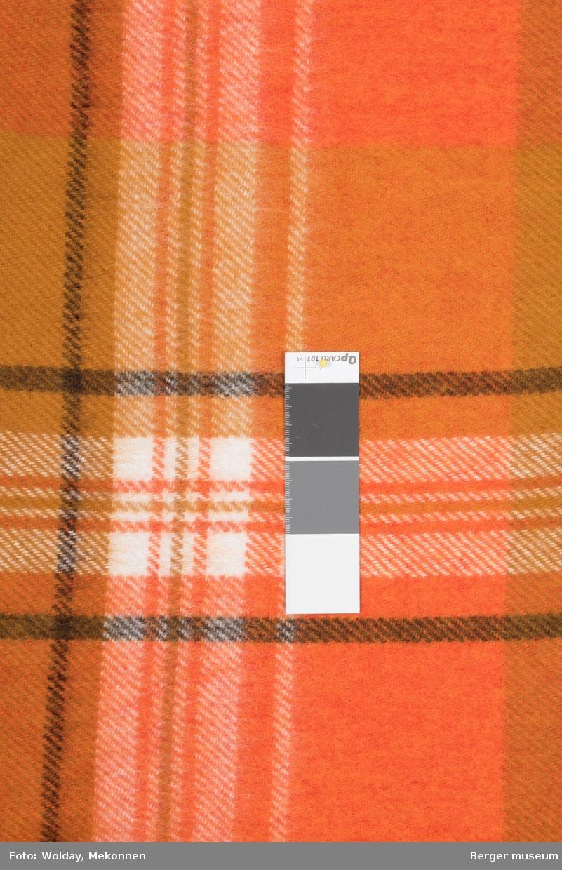 En pleddprøve i rutemønster. Prøven er klippet på tvers, slik at prøvens kortsider har jarekant  Mønsteret karakterisereres av rutemønster i rektangulære felt av varierende størrelse,  med smale striper horisontalt og vertikalt. En definert stripe med hvit renningstråd skaper tyldeige firkanter som er oppdelt av smale striper som krysses i firkanten. Uten frynser. I oransjetoner.