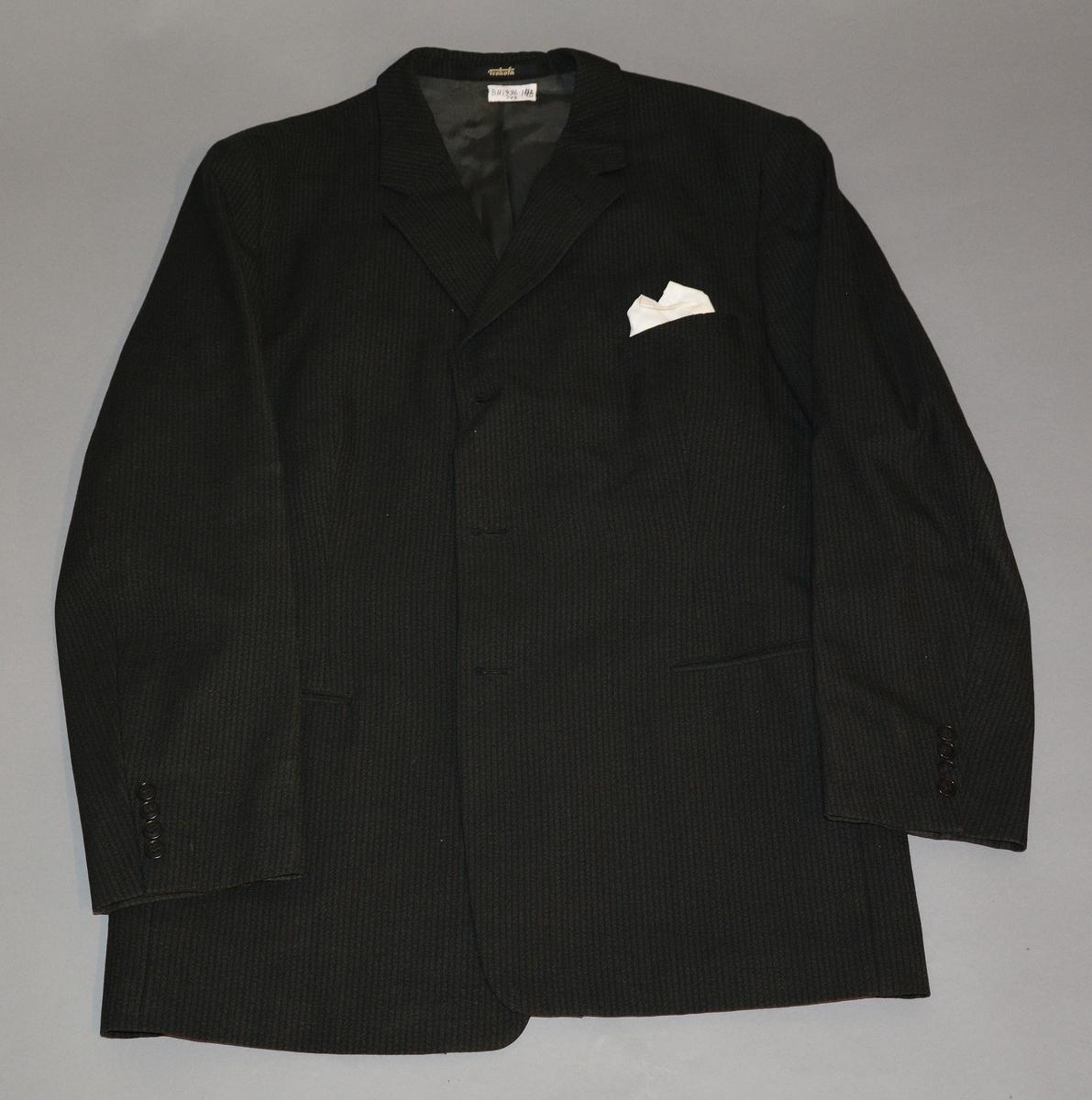 """Dress i mørkstripet ullstoff. Enkeltspent jakke med lett avrundede små slag. Merket på innsiden: """"Highest quality taylored by Trokota"""" Mellomstor størrelse."""