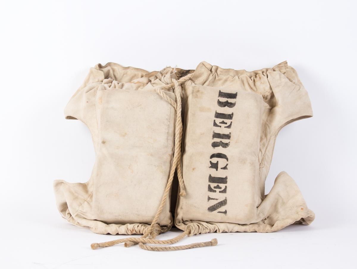 Livbelte fra LILLEGUTT av Bergen i kork og tøy. Livbelte er av bomullsstoff, der flyteposane er fylt med kork. Mellom dei 4 posane er der to hull til å tre armane gjennom, og tau til å knyte den sammen med foran på brystet.