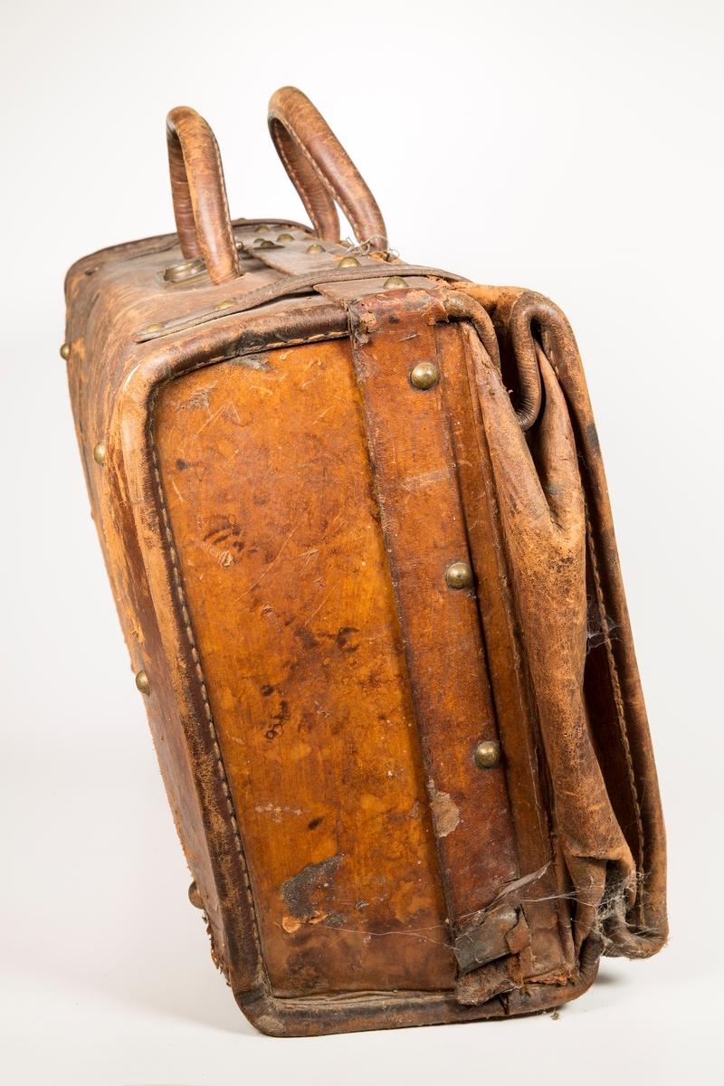 Kraftig reisekoffert av lær. Messinglås, dobbelt håndtak og to remmer over lokket. Innvendig trukket med papp, innerlokk med lærlomme.