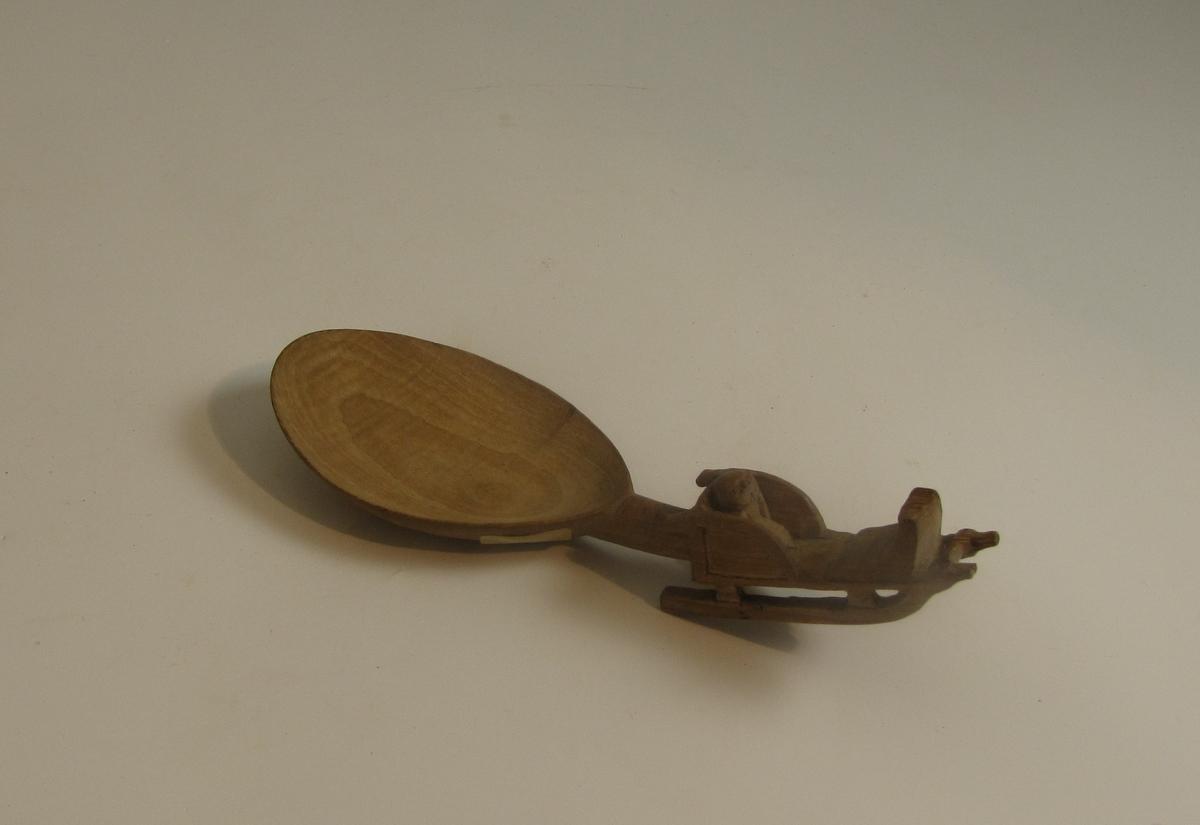 Utskåret treskei med skaft forma som en kjelke med et barn i. Innskripsjonen SSDH står for Siri Sveinungsdatter Heddeland.