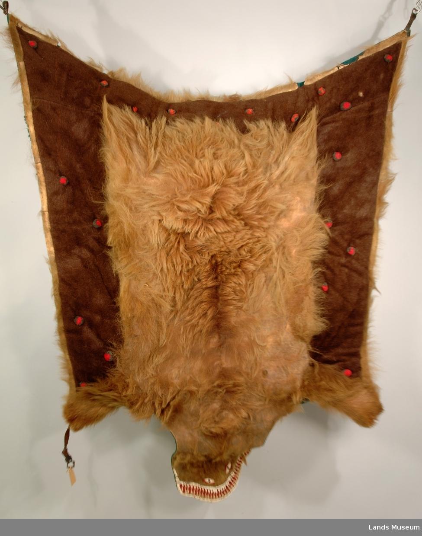 Bjørneskinn kantet med grønt ullstoff. Hodet er staffert med hvitt skinn og rød boy. Det er remmer til å spenne fellen fast.