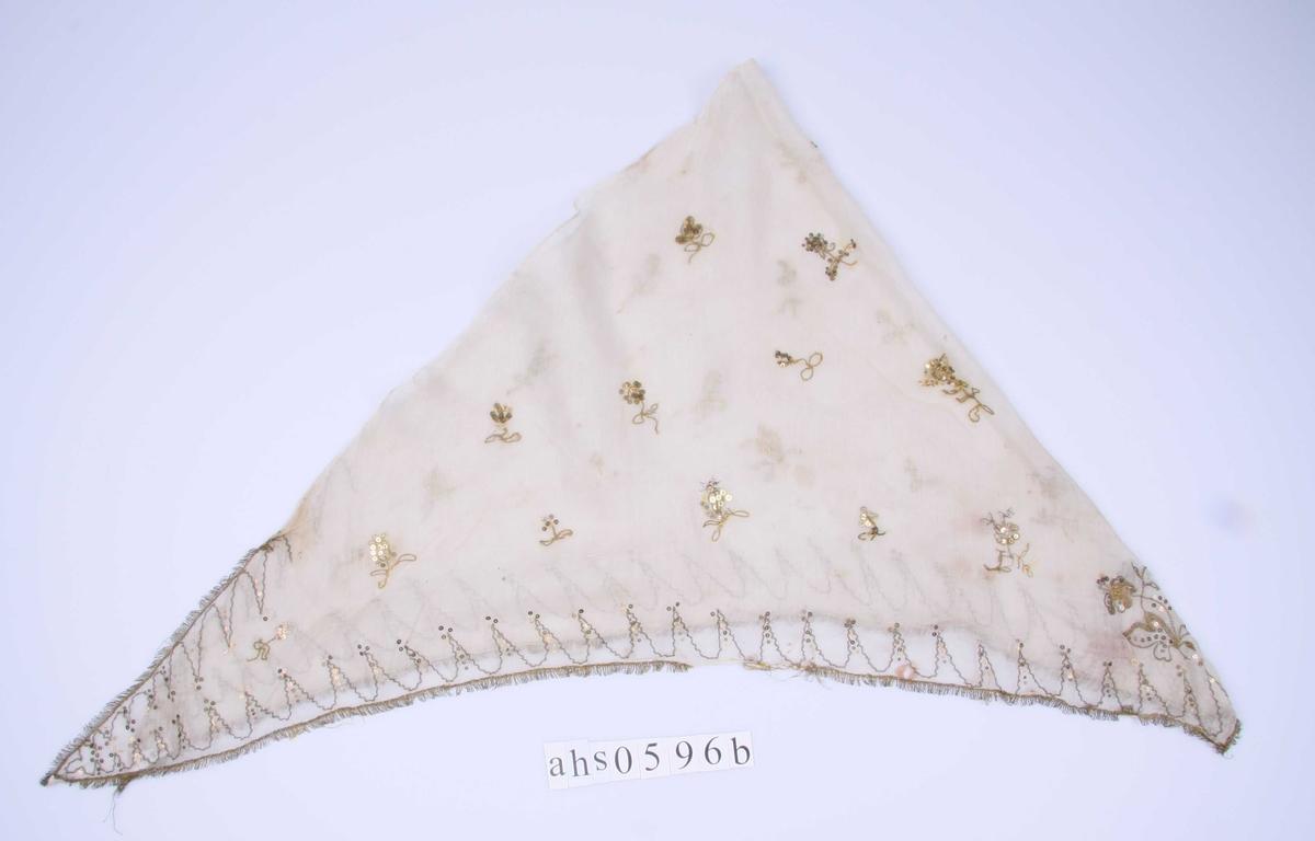 Sjal brukt sammen med kjole. Har antagelig vært brukt et trekantet tørkle av enda tynnere  bomullsmusselin. Det er kantet på kortsidene med en bølgebord av gulltråd og paljetter og små enkeltstilte blomster utover flaten.