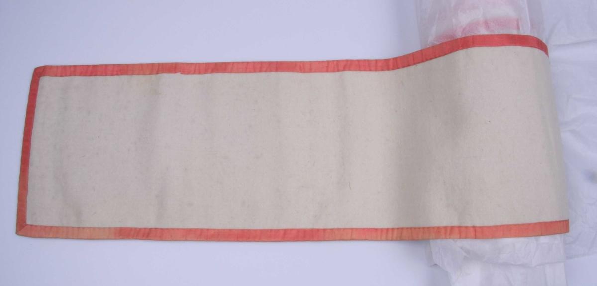 Av hvit vadmel med hvitt lerretsfôr og kant av laksrosa silkebånd.