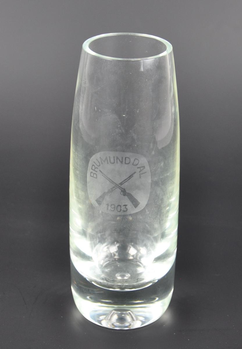 Blomstervase av glass med et emblem. I emblemet er det motiv av to gevær med innskrift Brumunddal 1903.