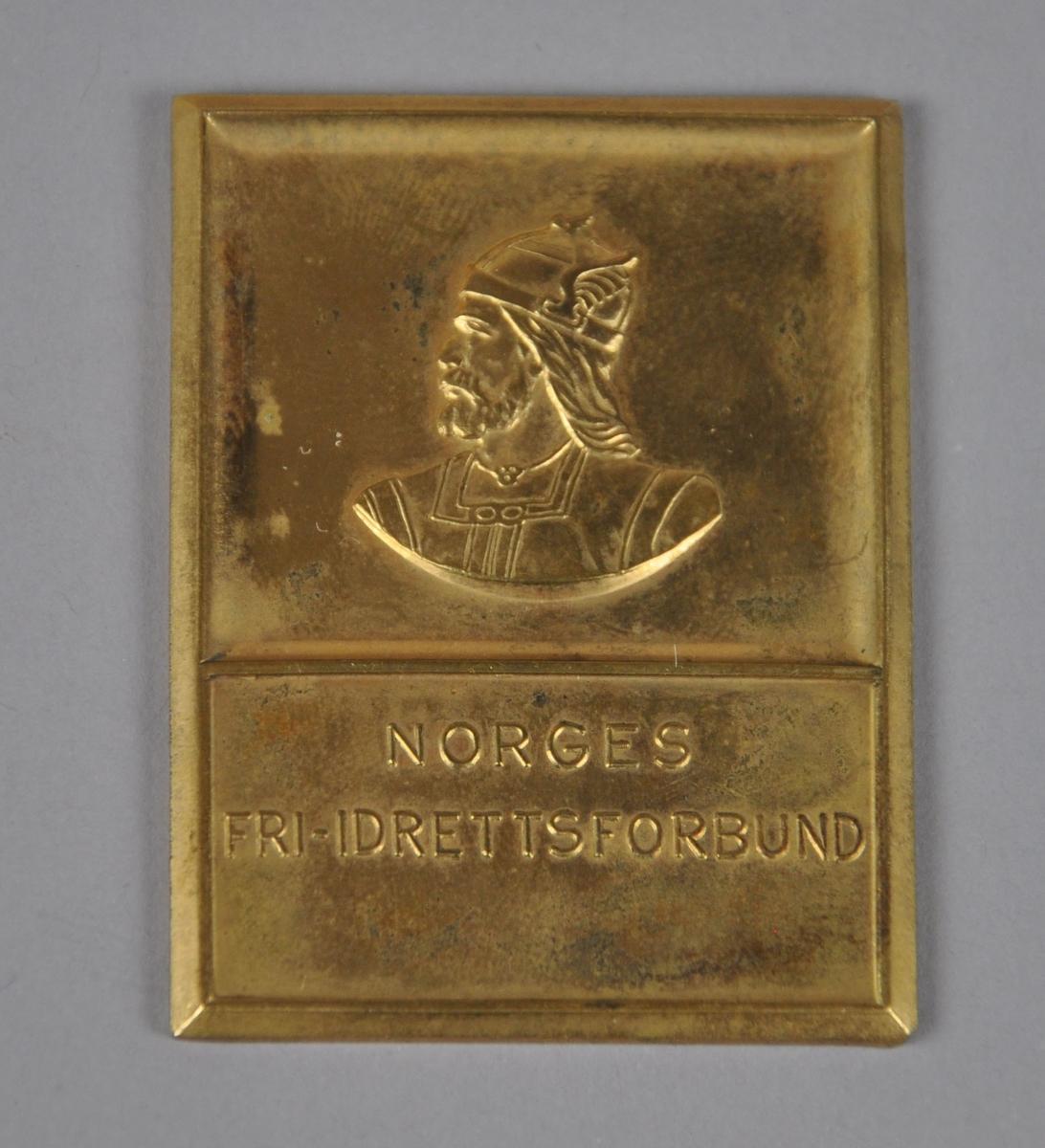 Medalje / plakett med bilde av en viking med hjelm og inskripsjon. Plaketten ligger i eske med gjenstandsnr. OLM-08236