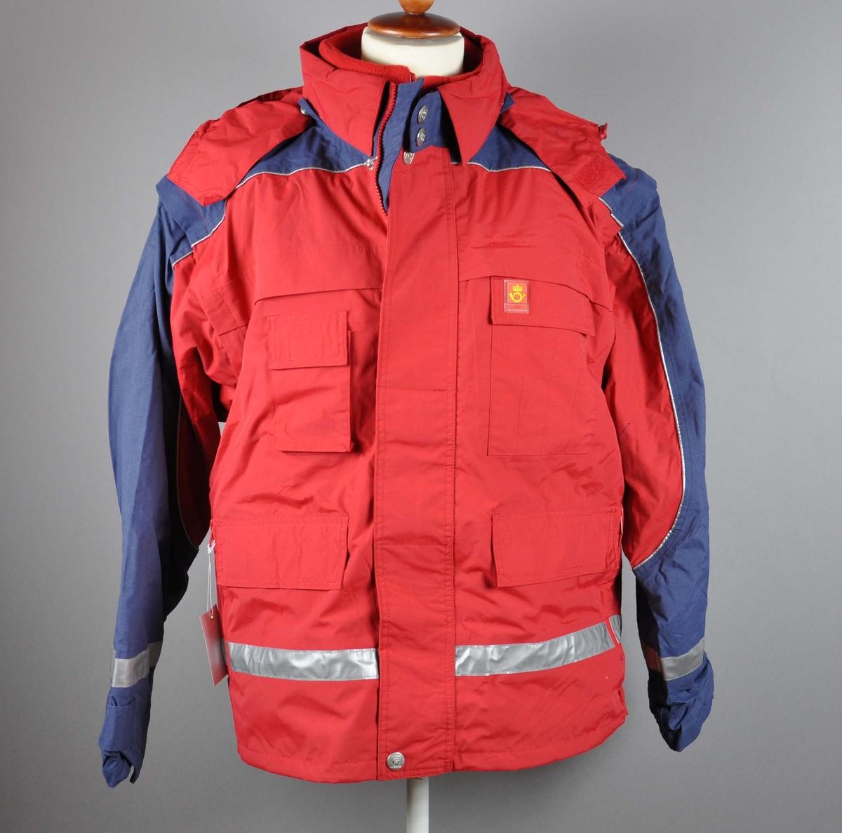 Rød uniformsjakke med påskrift og postlogo. 6 lommer og mobillomme. Med hette og avtagbart for. Refleksbånd i livet og på ermene.  Størrelse M- Mann 48, Dame 40.