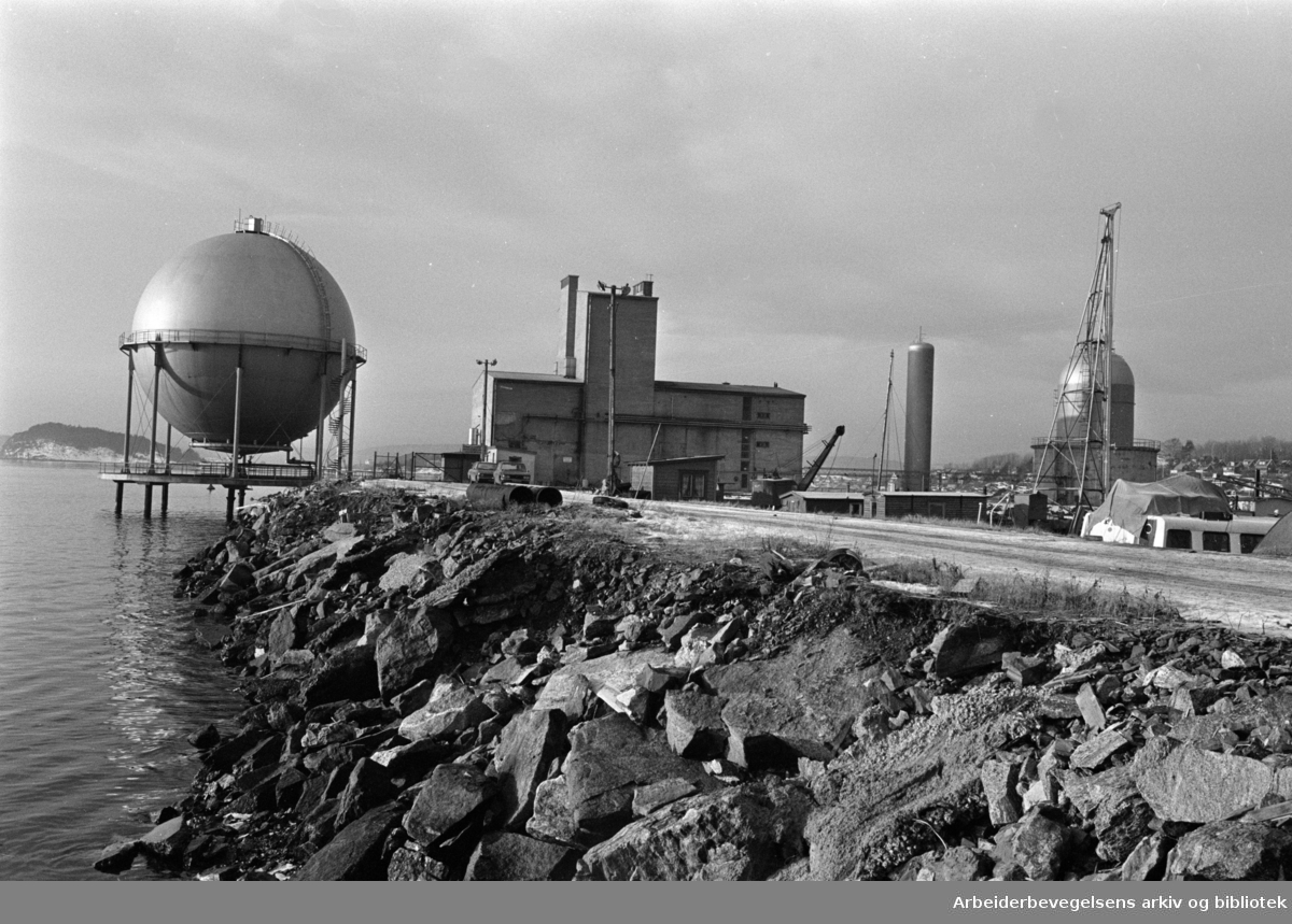 Sjursøya: Gassverket.Til venstre den karakteristiske gassbeholderen. Midt på bildet produksjonsbygningen hvor også administrasjonen har sin plass..Januar 1976