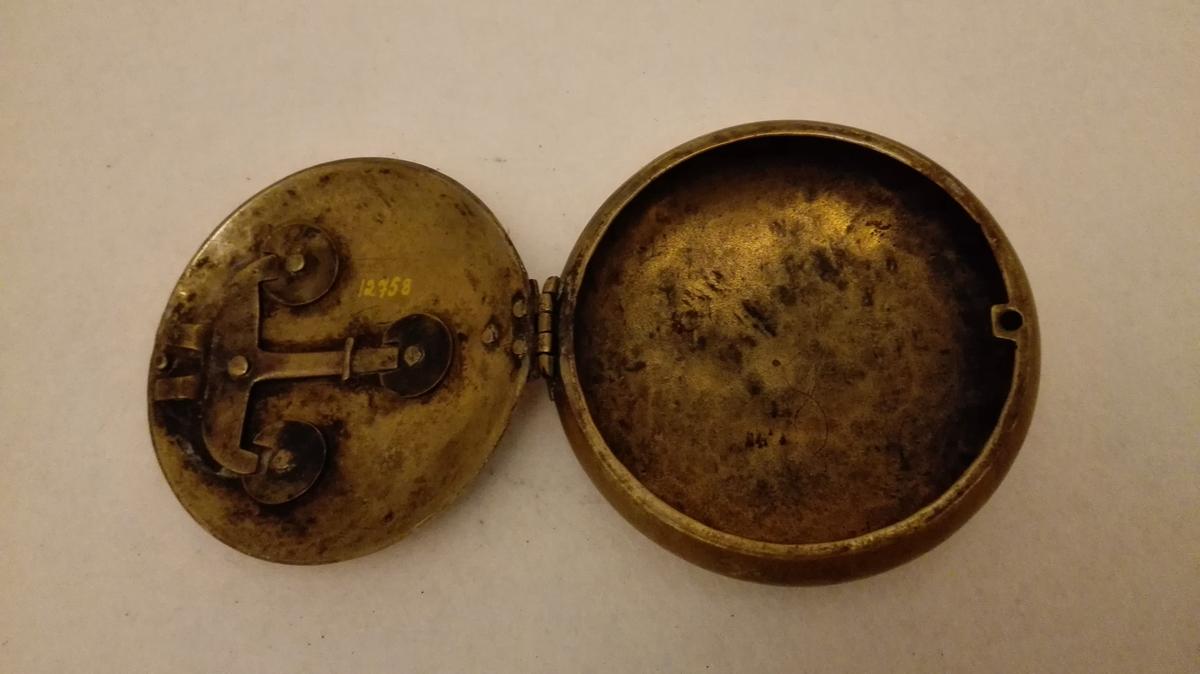 "1 messing snusdaase  Sirkelrund snusdaase av messing, diameter 9 cm. Laag og bund hvælvet. Paa laaget insdat en halvmaanefigur, en stjernefigur og 2 visere i en ""klokkeskive"", der alle fire danner laasemekanisme. Forat faa laaget op maa figurene stilles slik: Prikk paa stjerne mot prikk paa sirkelen omkring denne, höire viser maa peke paa 1/2 3, venstre viser maa peke paa IX, maanens ansikt maa snu helt til höire. Maanen föres saa ret op og laasen er oppe.  Gave fra planteskoleeier Arne Balvoll, Vik i Sogn."