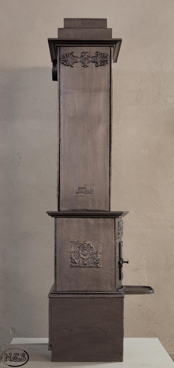 Ovnen består av to avdelinger. Underdelen har et frembuet midtparti med kamskjell flankert av sjødyr på hver side. På kortsidene skjold, løvehode og symmetriske ørner. På bakplate en krukke med symmetriske engler. Overdelen er høy, firkantet med tredelt åpning. Empire ornamentikk og avtrappet topp. Øverst på frontplaten symetriske fabeldyr (pegasus) vendt mot hverandre.