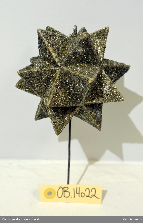 Stjerne med glitter til bruk på juletre, montert på metallstang.