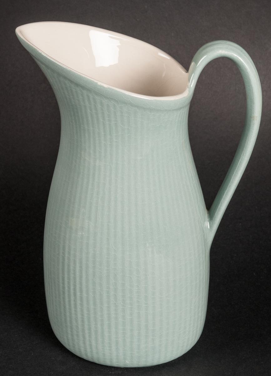 """Tillbringare av flintgods, modell -BA, formgiven av Arthur Percy för Gefle Porslinsfabrik. Smal, uppåtsträvande profil med lodgrepe. Aningen oval i formen. Buken vertikalt räfflad. Hög, uppåtböjd och spetsig snip. Glasyr """"Celadon 2"""", ingående i den ugnsfasta serien """"Corona"""" tillverkad 1955. Färgen grågrön, insidan gräddgul. Grön skorstensstämpel på vit grund med text """"Celadon Upsala-Ekeby Gefle Made in Sweden Percy"""". Vidare är """"Gefle eldfast"""" stämplat i massan."""