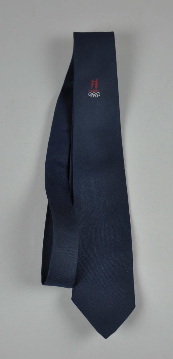 Blått slips  med NOK/NIFsin  logo i rødt og de olympiske ringene i hvitt.