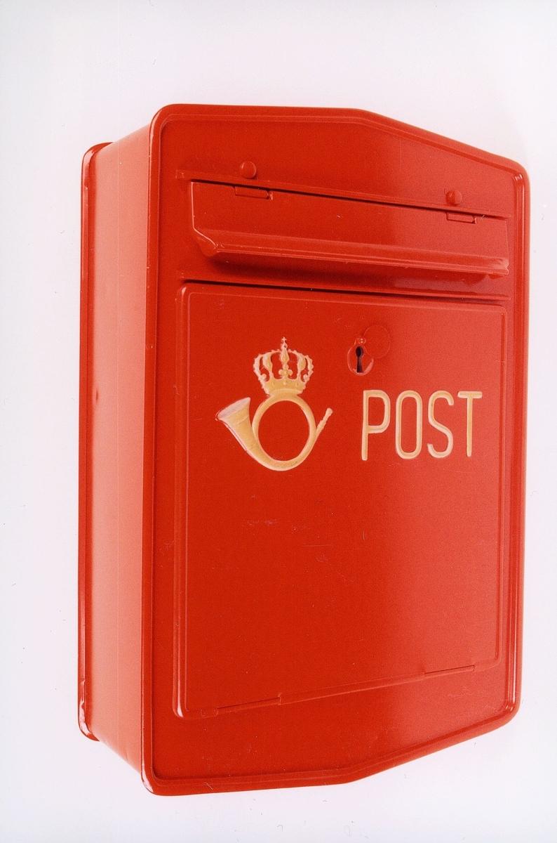 Rød, manuell tømmepostkasse med posthorn og ordet POST. Låsbar. Uten angivelse av tømmetider.