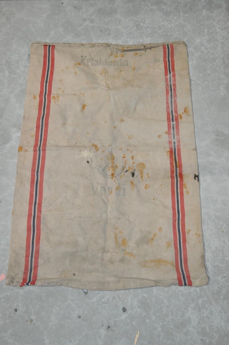 Postsekk laget av strie. Grå/gul farge med vertikale striper i rødt, hvitt og blått.