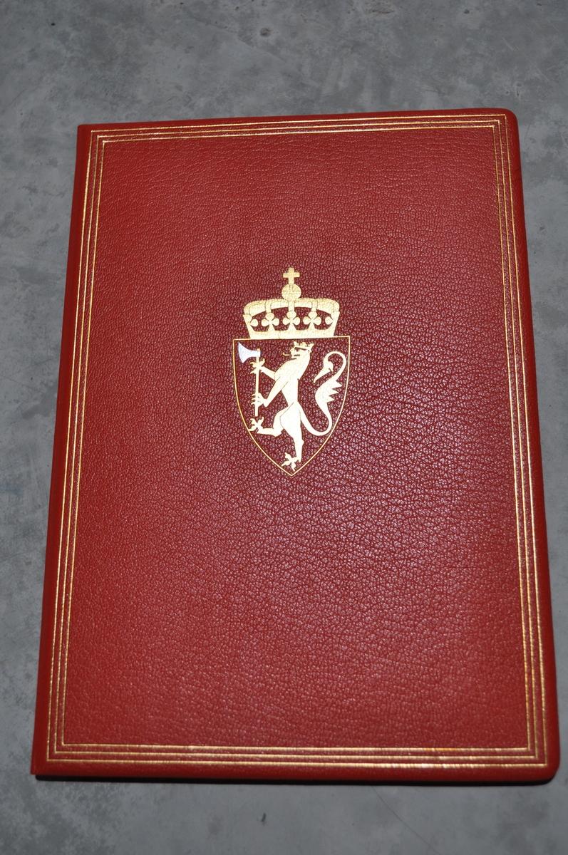 Rød skinnmappe med tekst på innsiden.