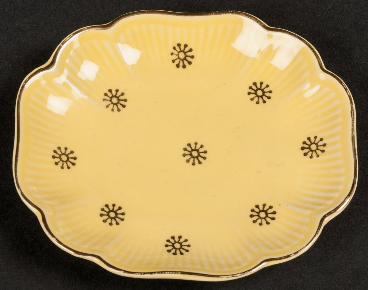 """Askfat av flintgods, litet, modell -A0. Ovalt med uppsvängt brätte, vågigt. Låg, rektangulär fotring. Formgiven av Arthur Percy. Dekor """"Neapel 2"""", handmålade, guldfärgade stjärnor och kantrand mot gul glasyrfond efter skiss av Percy. Guldfärgad skorstensstämpel under med text: """"Neapel Upsala-Ekeby Gefle Made in Sweden 250 1""""."""