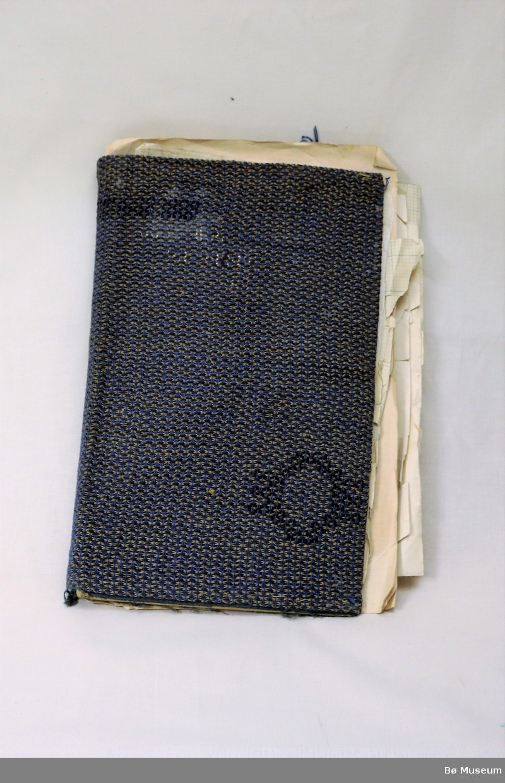 Bok med vevmønster. Omslaget på permen er fleirfarga og i gardin/portierestoff.