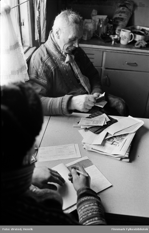 """Postfører Mathis Mathisen Buljo, bedre kjent som """"Post-Mathis"""" i samiske kretser, har levert post i en reindriftsenhet på Finnmarksvidda. Her sitter han med ryggen til mens postkunden studerer papirer han har fått av Mathis.   Fotograf Henrik Ørsteds bilder er tatt langs den 30 mil lange postruta som strakk seg fra Mieronjavre poståpneri til Náhpolsáiva, videre til Bavtajohka, innover til øvre Anárjohka nasjonalpark som grenser til Finland – og ruta dekket nærmere 30 reindriftsenheter. Ørsted fulgte «Post-Mathis», Mathis Mathisen Buljo som dekket et imponerende område med omtrent 30.000 dyr og reingjetere som stadig var ute i terrenget og i forflytning. Dette var landets lengste postrute og postlevering under krevende vær- og føreforhold var beregnet til 2 dager. Bildene gir et unikt innblikk i samisk reindriftskultur på 1970-tallet. Fotograf Henrik Ørsted har donert ca. 1800 negativer og lysbilder til Finnmark Fylkesbibliotek i 2010."""