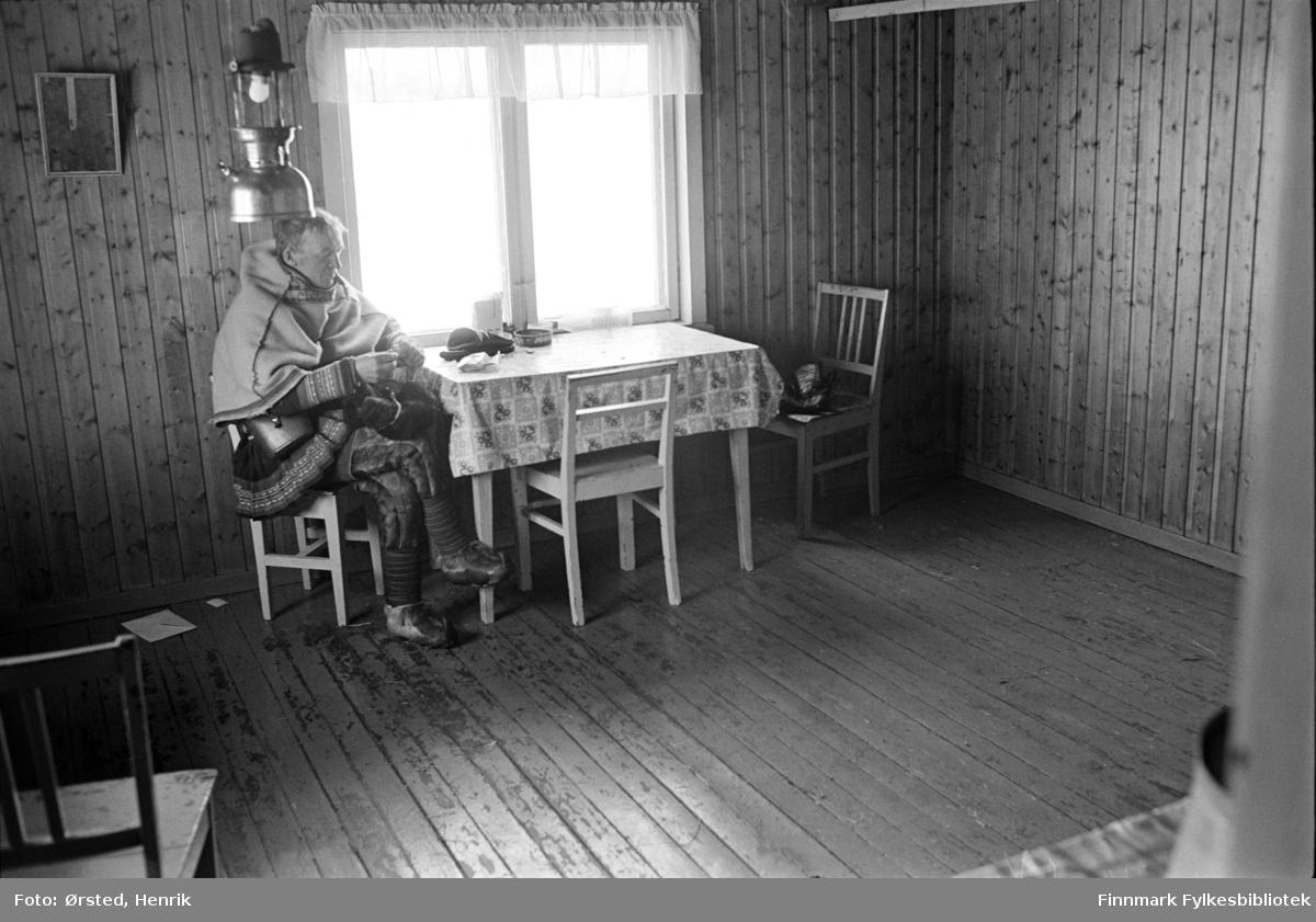 """Postfører Mathis Mathisen Buljo, bedre kjent som """"Post-Mathis"""" i samiske kretser, sitter alene ved kjøkkenbordet i et hus langs postruta. Han er i ferd med å rulle tobakk. Kanskje venter han på at reindriftsfolket skal komme inn fra arbeid på vidda?   Fotograf Henrik Ørsteds bilder er tatt langs den 30 mil lange postruta som strakk seg fra Mieronjavre poståpneri til Náhpolsáiva, videre til Bavtajohka, innover til øvre Anárjohka nasjonalpark som grenser til Finland – og ruta dekket nærmere 30 reindriftsenheter. Ørsted fulgte «Post-Mathis», Mathis Mathisen Buljo som dekket et imponerende område med omtrent 30.000 dyr og reingjetere som stadig var ute i terrenget og i forflytning. Dette var landets lengste postrute og postlevering under krevende vær- og føreforhold var beregnet til 2 dager. Bildene gir et unikt innblikk i samisk reindriftskultur på 1970-tallet. Fotograf Henrik Ørsted har donert ca. 1800 negativer og lysbilder til Finnmark Fylkesbibliotek i 2010."""