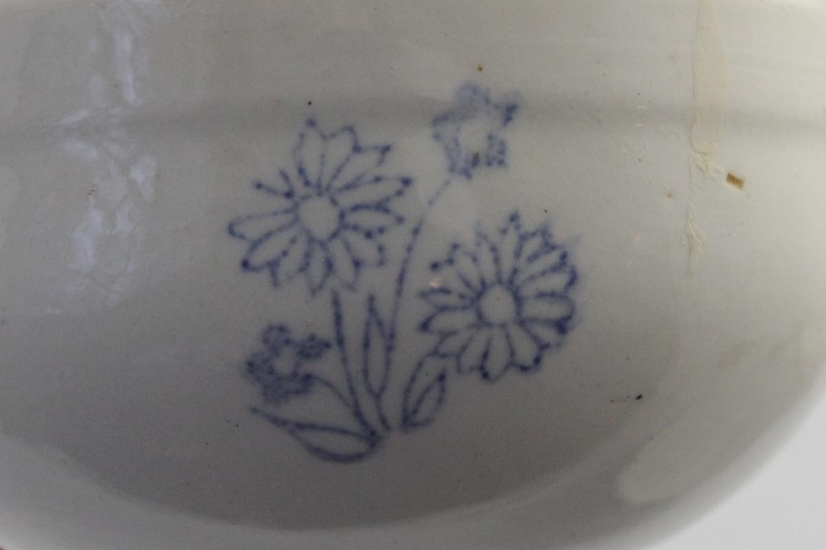 Liten bolle i steintøy, brukt til matlaging/husholdningsbruk. Hvit bunn med blå dekor. Fire blomsterbuketter jevnt plassert på utsiden.
