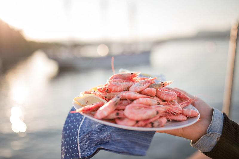 Hånd holder hvit tallerken med reker og med en blå serviett under, diffust seilskip i bakgrunnen.