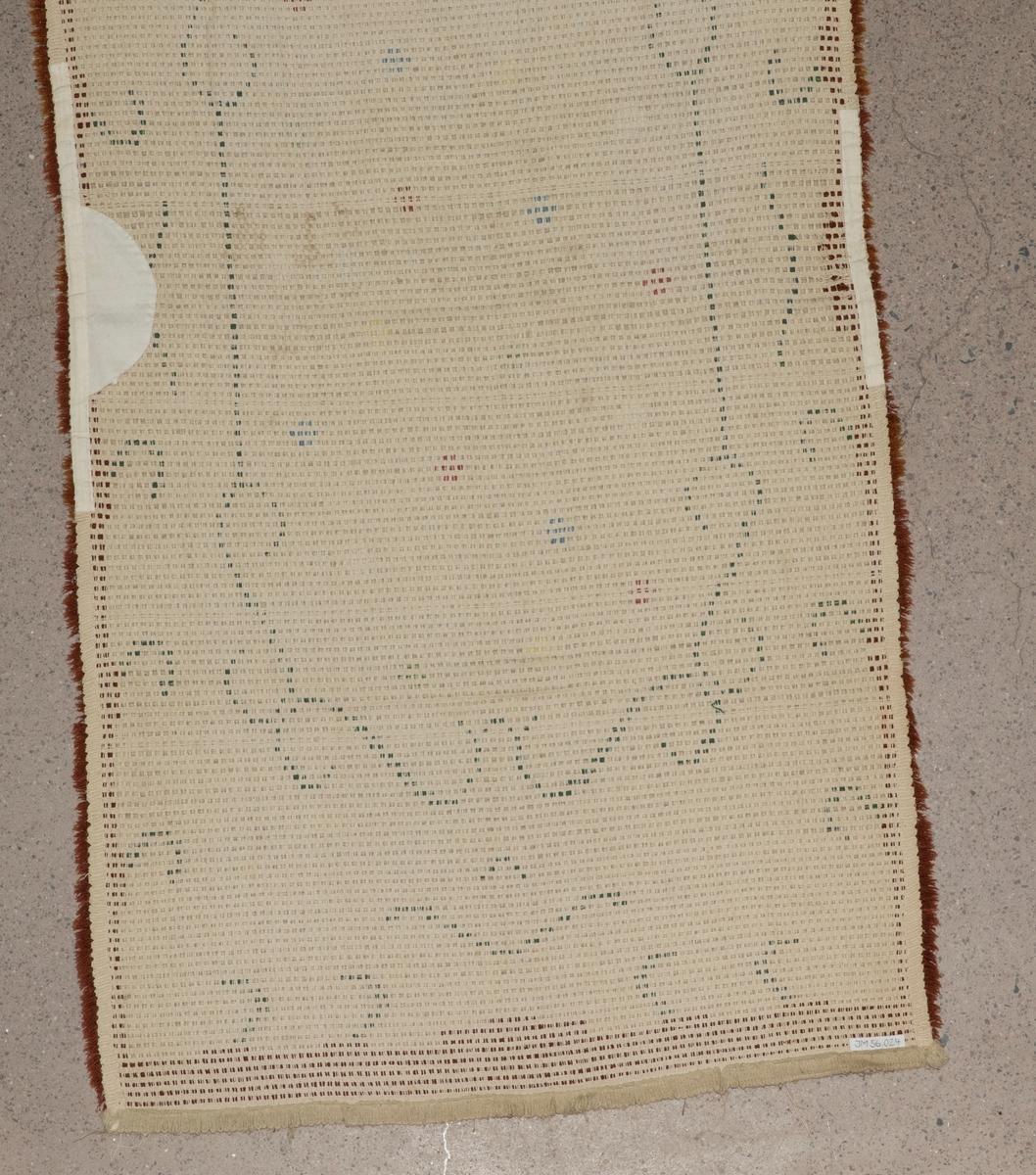 """Matta vävd i flossateknik, varpen är av bomull och inslaget av ylle. Mattan är rektangulär med beige botten med möster i form av gröna slingor och korsformade """"blommor"""" i grönt, blått, rosa, gult och beige. Runt mattans kanter är en ram i rost-brun färg. På baksidan är mattan förstärkt på ett par ställen med bomullsband och tyg."""