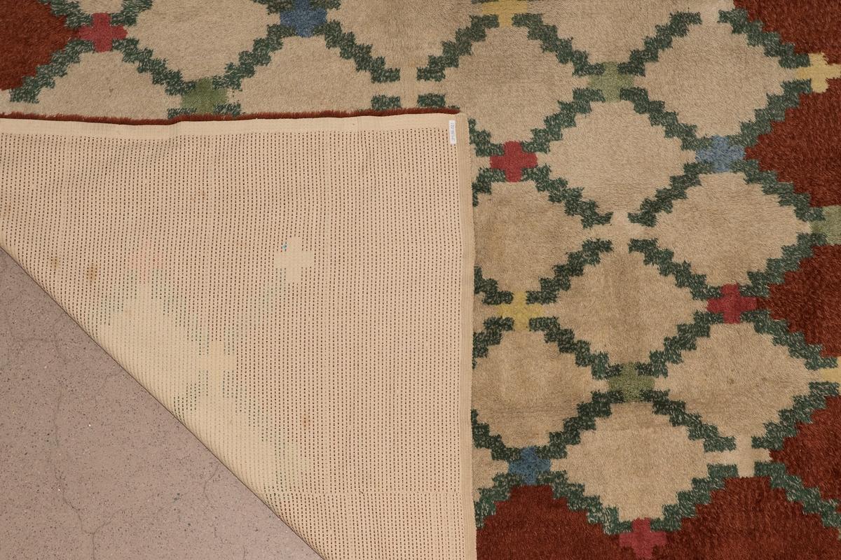 """Matta vävd i flossateknik, varpen är av bomull och inslaget av ylle, Mattan har ett geometriskt romb-mönster i grönt och beige med korsformade """"blommor"""" i blått, grönt, rosa, gult och beige. Runt mattans kanter är en ram i rost-brun färg, som går in flikformat i mönstret. Kortändarna har stadkant. Mattan är väv i tre längder (vävd i 90 cm bred vävstol), vilka är ihopsydda."""