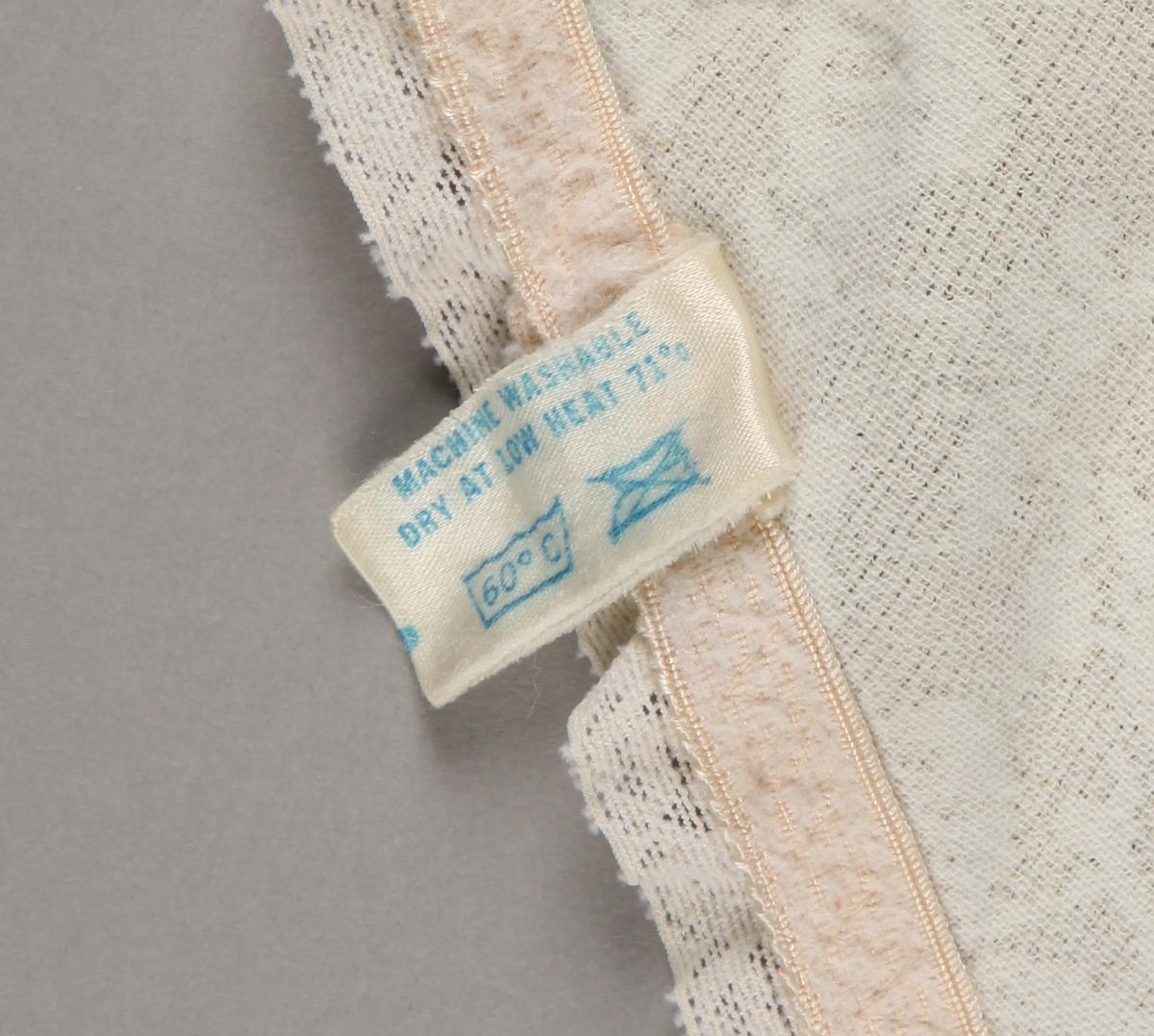 Korselett i blondevevd stoff med sateng panel. BH-del i blonde og hudfarga bomull (?). Lukking med 3 hekte under skrittet. Ingen stropper. Storleik 38C.