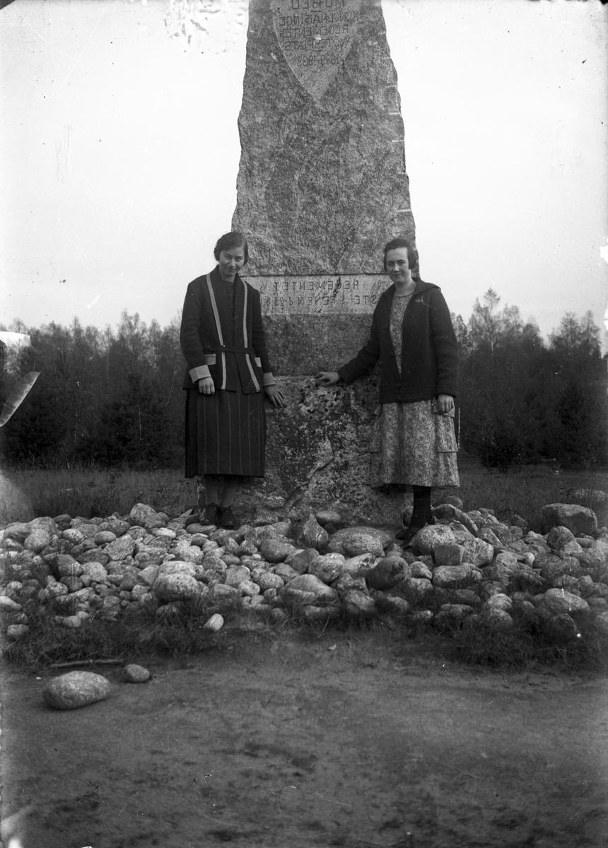 Två kvinnor vid Mohed regementes monument (sten).