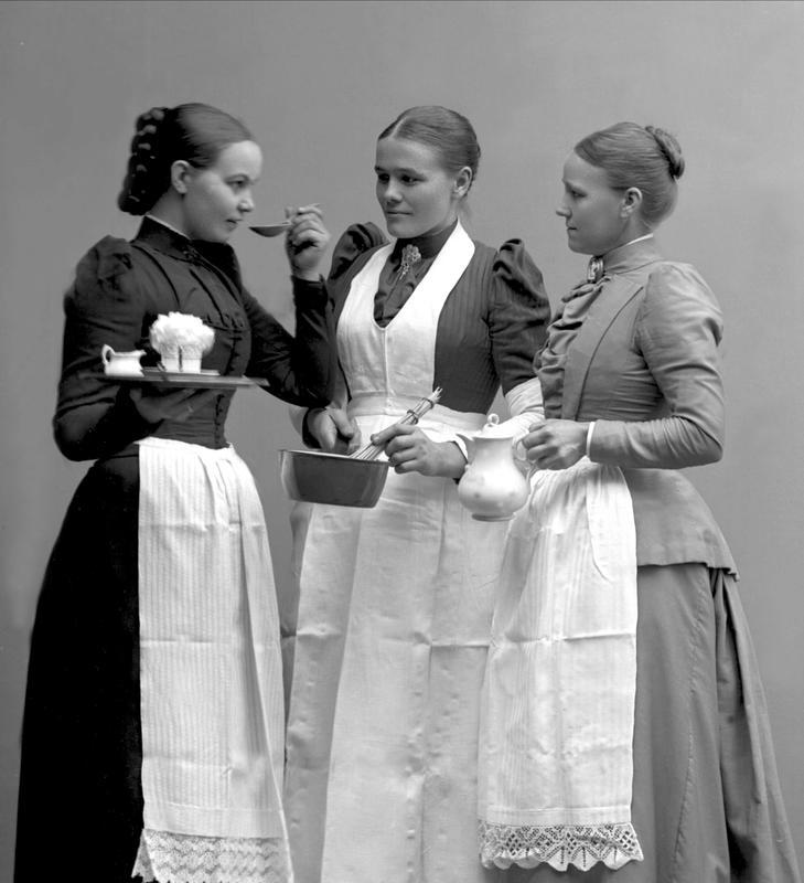 Dette arrangerte gruppeportrettet tatt i  fotograf Borgens atelier i Kristiania viser tre unge tjenestejenter i strøkne serveringsforklær.